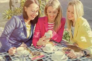 Woman showing pictures to her friends on mobile phone
