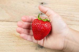 One strawberry held by a hand. photo