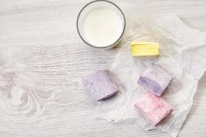 Some pastel colored marshmallows top view with glass of milk photo