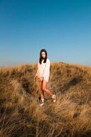 Pretty black girl posing in dune landscape.