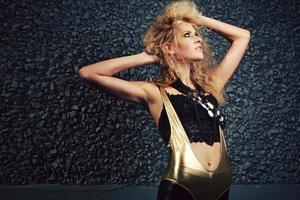 Golden Unitard Blonde Girl on Black Holding Big Hair photo