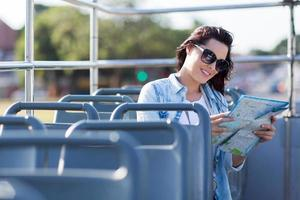 tourist looking at map on open top bus