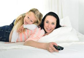 young mother holding remote control and daughter watching television together photo