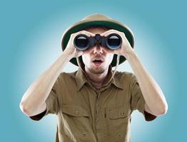 Surprised explorer looking through binoculars