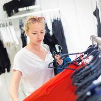 Hermosa mujer de compras en la tienda de ropa. foto