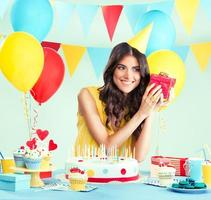 Beautiful woman holding a present at her birthday party photo