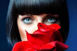mooie brunette achter rode roos in studio