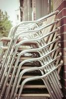 Pila de sillas de aluminio de un restaurante.