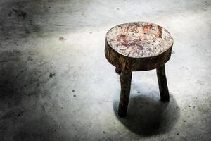 banquinho de madeira velho no chão de cimento na luz