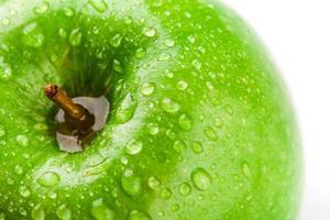 manzana en verde con gotas de agua en su superficie foto