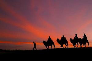 great sky and caravan travelers riding camels photo