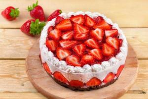 Yogurt cake with strawberries on wood table