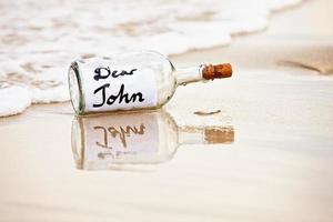 Dear John starts break-up message in washed-up bottle on beach photo