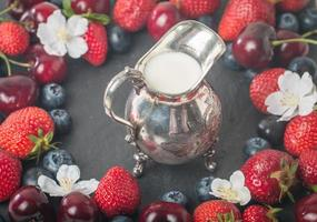 frame of fresh berries with creamer
