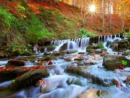 Beautiful waterfall in forest at sunset photo