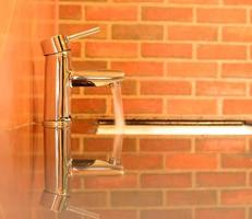 metal faucet with flowing water