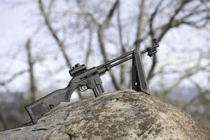 Rifle on top rock in forest stationary photo