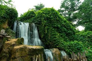 Waterfall in forest against white sky