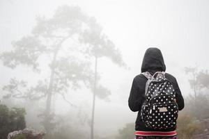 Backpacker walking through a misty forest photo