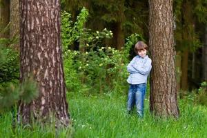 Little boy playing in a beautiful forest