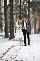 Bride and groom walking in winter forest