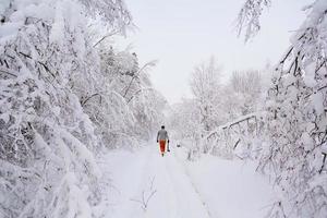 leñador camina en un bosque nevado foto
