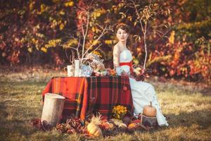 noiva sentada perto da mesa na floresta de outono
