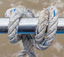 nudo de cuerda atada alrededor del soporte de acero en barco o yate foto