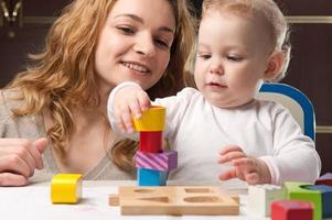 Baby, das mit Mutter einen Turm aus Holzklötzen baut