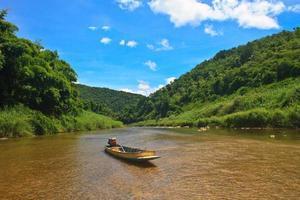 río en bosque siempre verde con barco