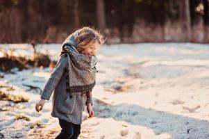 niña niña caminando por la carretera en el bosque de invierno