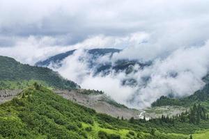 Morainic glacier winding river among mountain alpine forest photo