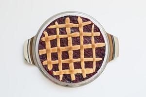 Lattice cake with forest berries against white background