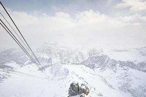 Cable cars running through snow covered mountains photo