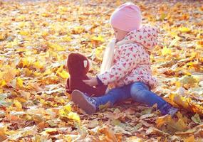 Cute little girl playing in the leaves photo