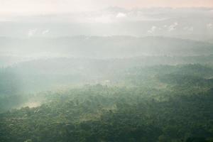 la luz del sol brilla a través de las nubes hacia las montañas y el bosque