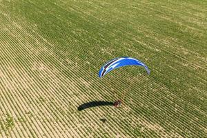 aerial view of paramotor flying over the fields