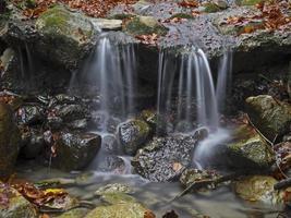 Falling water in autumn forest, Wasserfall im herbstlichen Wald