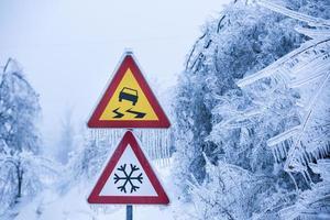 strada pericolosa e ghiacciata con alberi coperti di nevischio
