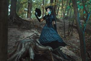 Girl in gothic dress standing among the snags forest.
