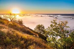 amanhecer enevoado da colina sobre o vale e a floresta
