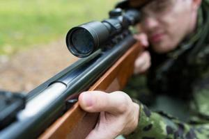 close up of soldier or hunter with gun in forest photo
