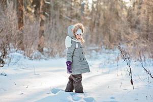 niedliches Kindermädchen, das im sonnigen Winterwald steht