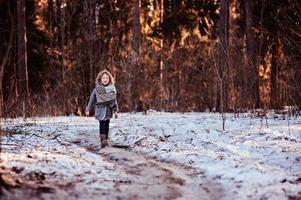 child girl walking the road in winter forest photo