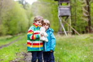 Two kid boys walking through forest on cold day