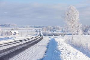 Líneas de carretera de invierno de asfalto a través del campo rural en el horizonte