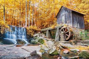 Fall or Autumn image of historic mill and waterfall
