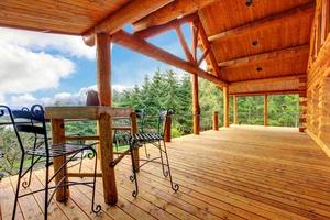 Porch of  log cabin with small table and forest view.