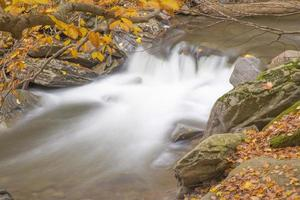 Small, frozen, waterfall in slow motion with yellow Autumn forest