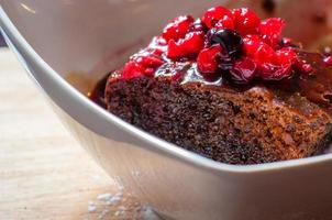 Close-up on chocolate cake with forest fruits, food background